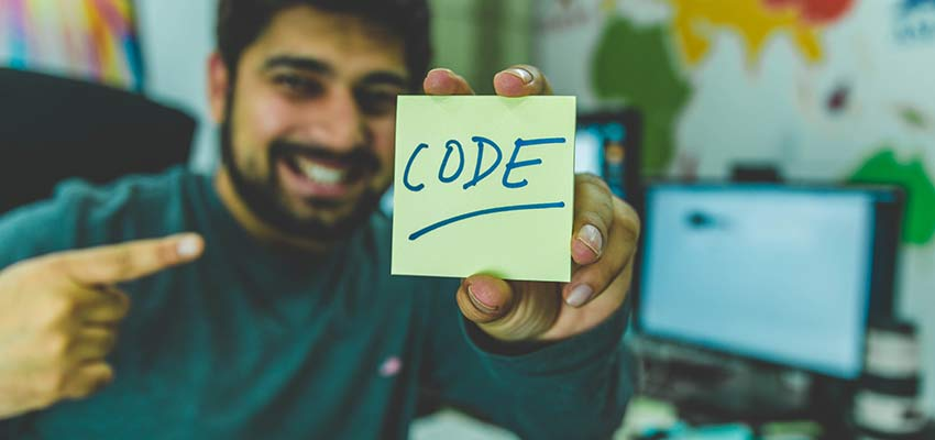 "Man holding a note that says ""Code""."