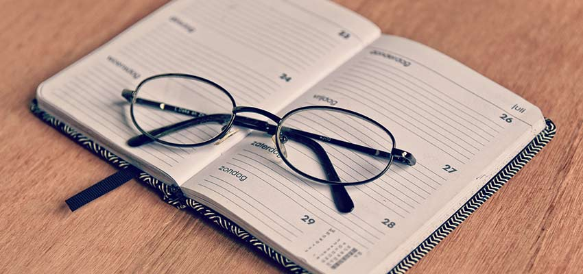 A pair of glasses on top of a planner.