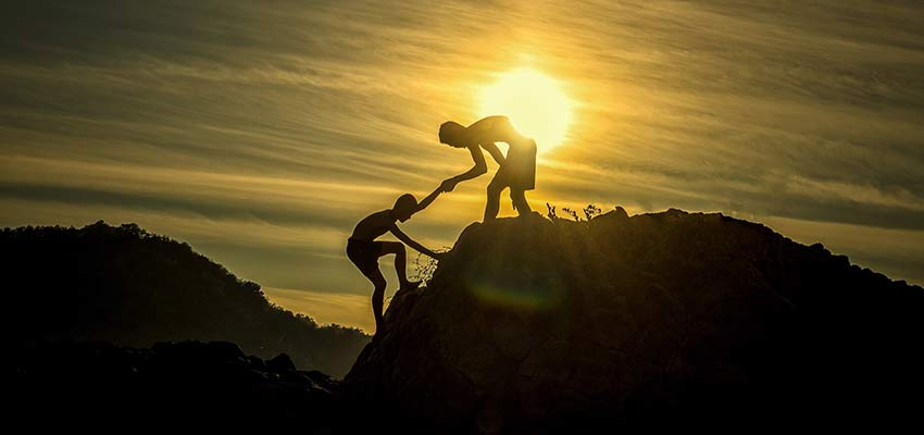 Person helping another to climb a hill.