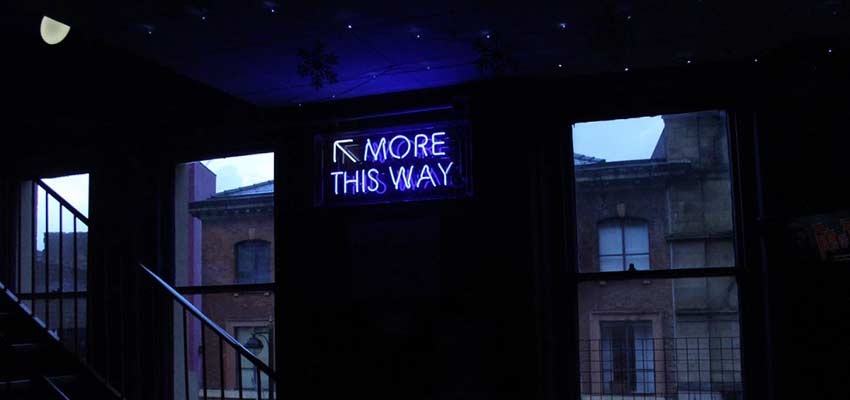 "A neon sign that reads ""More This Way""."