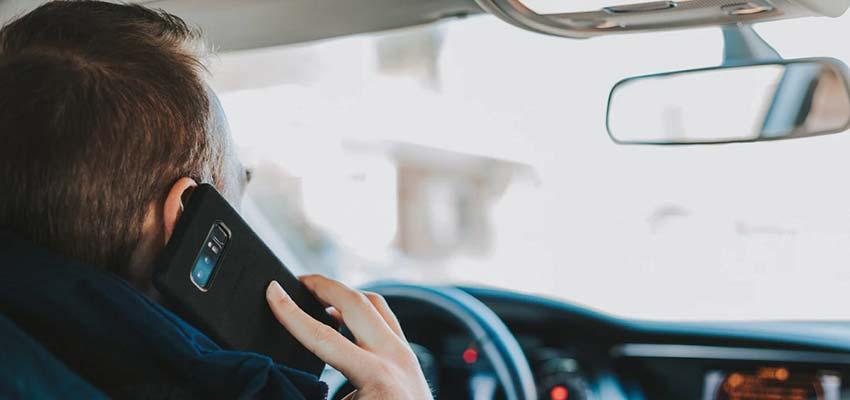 Man on a cellphone inside a car.