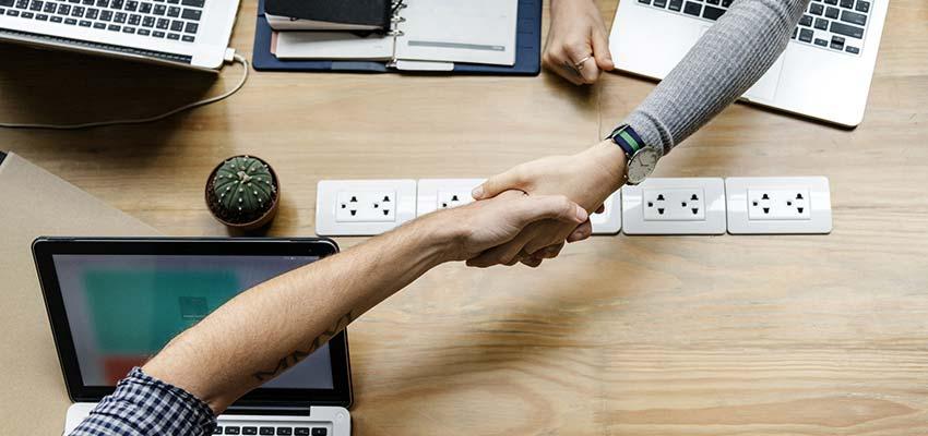People shaking hands across a desk.