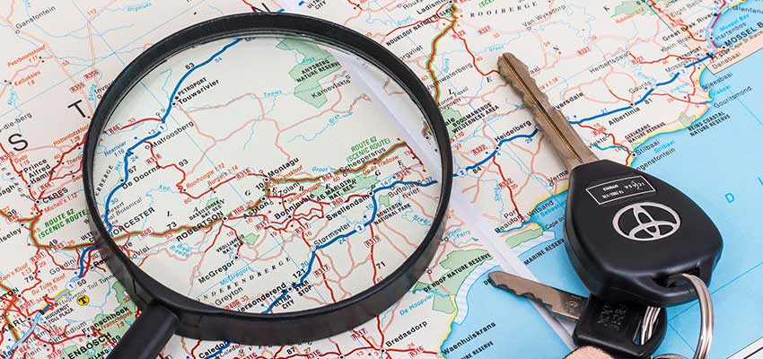 A map with a magnifying glass and car keys.