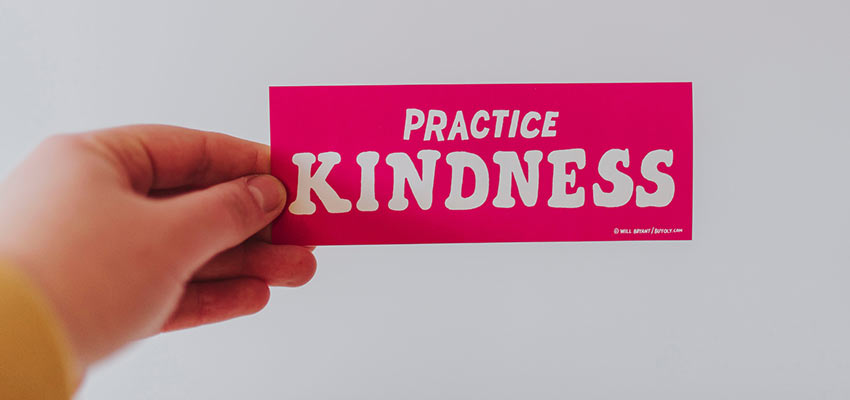 "Person holding a bumper sticker that reads ""Practice Kindness""."