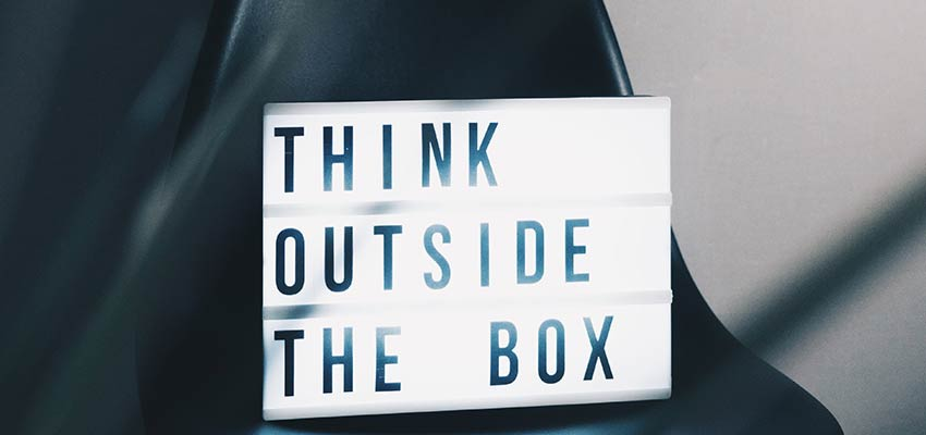 "A sign that reads ""Think Outside the Box""."
